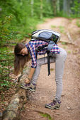 Woman with backpack hiking into the forest — Stock Photo