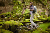 Woman hiker crossing the river — Stock Photo