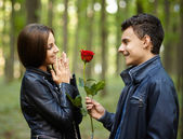 Teenager giving a flower to his girlfriend — Stock Photo