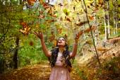 Woman throwing leaves in the air — Stock Photo