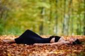 Beautiful woman in black dress in park — Stock Photo