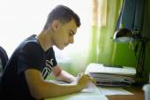 Teenage boy doing homework — Stock Photo