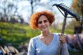 Woman with rake cleaning garden — Stock Photo