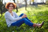 Lady farmer sitting in the grass — Stock Photo