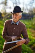 Old farmer sharpening scythe — Stock Photo