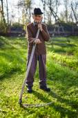 Farmer mowing lawn with scythe — Stock Photo