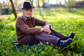 Old farmer sitting in grass — Stock Photo