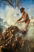 Old farmer burning dead leaves — Stock Photo