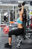 Fitness girl doing shoulder workout — Stock Photo