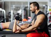 Fitness instructor assisting young woman — Stock Photo