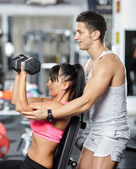 Fitness trainer helping girl in a gym — Stock Photo