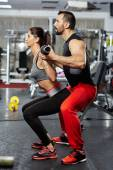 Doing squats with barbell helped by personal instructor — Foto de Stock