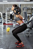 Fitness girl doing barbell squats — Stock Photo