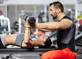 Personal trainer assisting young woman — Stockfoto