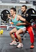 Athlete doing assisted barbell squats — Stock Photo