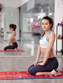 Fitness girl resting on a yoga mat in a gym — Stock Photo