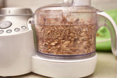 Crushed kernel walnuts in food processor — Stock Photo