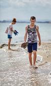 Family walking barefoot on the beach — Stock Photo