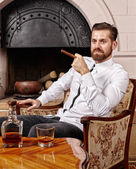 Businessman relaxing with a glass of scotch and a cigar — Stock Photo