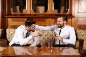 Two friends having a glass of whiskey — Stock Photo