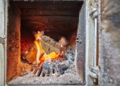 Burning fire inside a heater with stove — Stock Photo