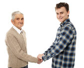 Grandfather and grandson shaking hands — Stock Photo