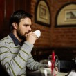 Young man drinking coffee in a restaurant — Stock Photo #70315793