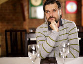 Young handsome man sitting in a restaurant — Stock Photo