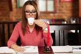 Young woman drinking coffee in a restaurant — Stock Photo