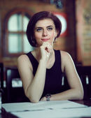 Young beautiful woman waiting in a restaurant — Stock Photo