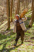 Senior woodcutter carrying a log on shoulder — Stock Photo