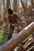 Old woodcutter at work with chainsaw — Stock Photo