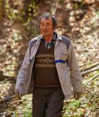 Old caucasian woodcutter moving in the forest — Stock Photo