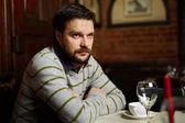若い男がレストランでコーヒーを飲む — ストック写真