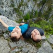Father and son sitting on the edge of a cliff — Stock Photo #72466407