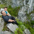 Father and son sitting on the edge of a cliff — Stock Photo #72466413
