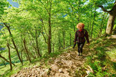 Woman with backpack on a forest trail — Stock Photo