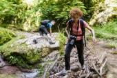 Family of hikers crossing the river — Stock Photo
