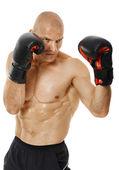 Very fit kickboxer punching — Stock Photo