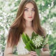 Portrait of beautiful young woman with lily of the valley — Stock Photo #75587215