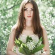 Portrait of beautiful young woman with lily of the valley — Stock Photo #75587217