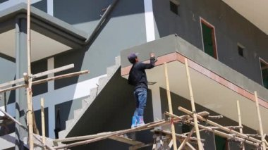Young man produces plastering on construction — Stock Video