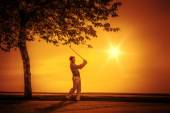 Golf player sunset — Stock Photo