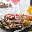 Dish with meat and vegetables served with rose wine — Stock Photo #57301453