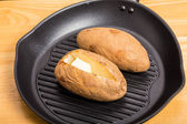 Baked Potatoes in Black Iron Skillet — Stock Photo