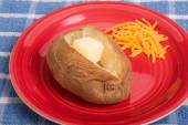 Baked Potato with Butter and Grated Cheese on Red Plate — Stock Photo