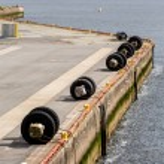 Tire Bumpers Along Concrete Pier — Stock Photo #74406065