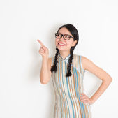 Asian Chinese girl pointing on blank copy space — Stock Photo