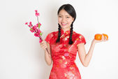 Asian chinese girl holding tangerine orange and plum blossom — Stock Photo