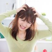 Asian woman scratching itchy head — Stock Photo